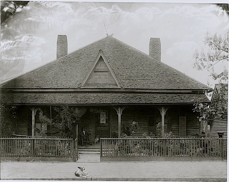 House with picket fence, man and dog seated on the porch.