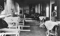 """Furniture on the verandah of a Queenslander home, ca. 1925."""