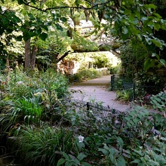 A footbridge passes over one end of the garden.